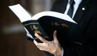 A suited man visible from the shoulders down holding a legal book with Chinese characters on the cover