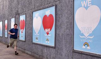 Man running past 'We love NHS' signs