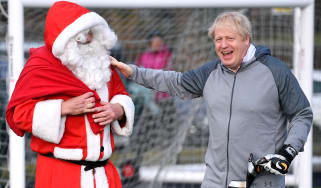 CHEADLE HULME, UNITED KINGDOM - DECEMBER 07: British Prime Minister Boris Johnson greets a man dressed as Father Christmas during the warm up before a girls' soccer match between Hazel Grove