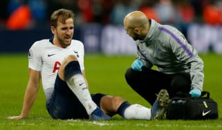 Tottenham Hotspur striker Harry Kane receives treatment for his injured ankle