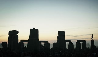 A man stands on top of one of the stones in Stonehenge on summer solstice
