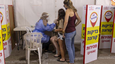 A health worker takes a swab sample for Covid-19 rapid antigen testing in Tel Aviv on 24 August 2021