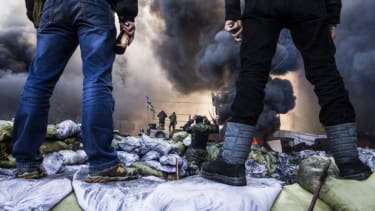 Anti-government demonstrators stand on barricades during clashes with riot police in Kiev on February 18, 2014. Opposition leader Vitali Klitschko on February 18 urged women and children to l