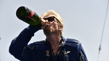 Richard Branson drinks champagne after  inaugural flight into space aboard Virgin Galactic vessel