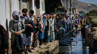 Afghans make their way through a flooded street towards Kabul airport
