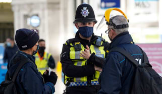 A member of the British Transport Police speaks with travellers at Waterloo Station
