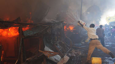 A man tries to put out a fire in the Deep Sea slum in Nairobi.