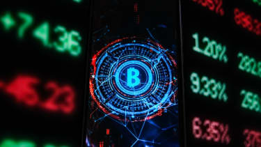 A Bitcoin logo is seen displayed on a smartphone with stock market percentages on the background