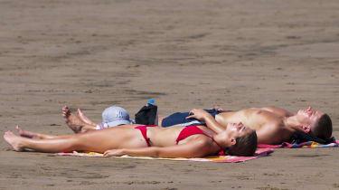 Couple sunbathing on beach in Wales