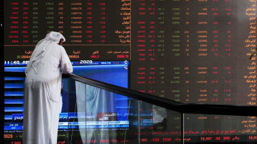 A Kuwaiti trader checks stock prices at Boursa Kuwait in Kuwait City, on March 8, 2020. - Kuwait Boursa authorities stopped trading after the Premier Index slumped 10 percent while the All-Sh