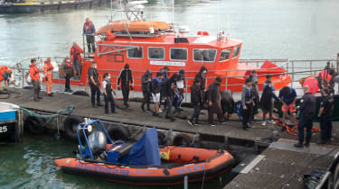 Migrants disembark from a vessel in Calais