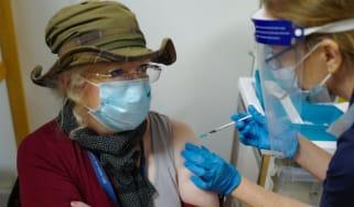 An NHS nurse vaccinates a patient