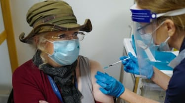 An NHS nurse vaccinates a patient with the Pfizer Covid vaccine