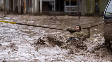A man clings to a security line to cross a street flooded by the overflowing of the Copiapo River due to heavy rainfall that affected some areas in the city, in Copiapo, Chile on March 26, 20