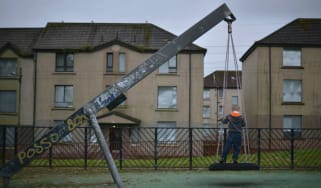 A young boy plays in a park near disused housing in Glasgow, Scotland