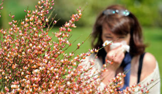 A woman with hayfever blows her nose