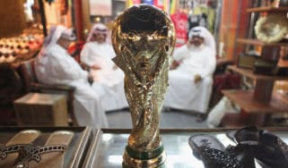Men sit at a market stall in Qatar with a replica of a trophy