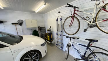 A garage with a parked car and racks for bicycles and tools