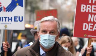 Anti-Brexit demonstrators hold placards as EU chief negotiator Michel Barnier walks through central London.
