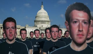 Protesters don Mark Zuckerberg mask before his Senate hearing