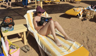 A holidaymaker reads a book