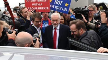 Britain's main opposition Labour Party leader Jeremy Corbyn (C) leaves after an interview with the BBC during the Labour party conference in Brighton, on the south coast of England on Septemb