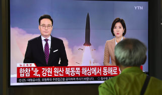 A man watches a television news screen reporting latest developments on North Korea's missile launch as the screen shows file footage, at a railway station in Seoul on October 2, 2019. - Nort