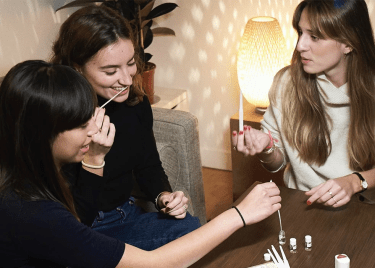 Three women at a table trying perfume samples