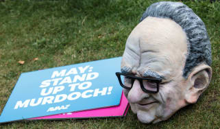 A puppet head of Rupert Murdoch sits next to an anti-takeover placard outside Parliament