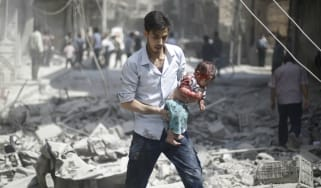 A Syrian man carries a wounded baby following a nair strike by Syrian government forces in the rebel-held area of Douma