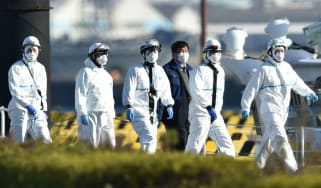 Officials at the Japan Coast Guard base in Yokohama where a cruise ship is in quarantine following an outbreak of coronavirus
