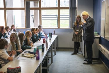 COALVILLE, ENGLAND- AUGUST 26: British Prime Minister Boris Johnson, wearing the school tie he was presented with on arrival, speaks to a class of year 7 pupils on their first day back at sch