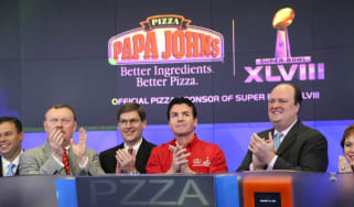 John H. Schnatter, Founder, Chairman & CEO of Papa John's International, Inc. (C), with David Wicks of Nasdaq (2nd R) and rep