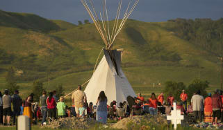 First Nation Canadians gather for a vigil on the site of a burial site in Saskatchewan