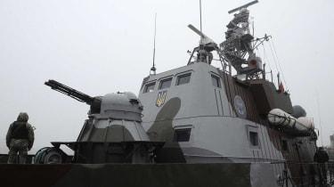 A Ukrainian sailor patrols a gunboat on the Sea of Azov