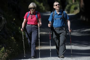 British Prime Minister Theresa May (L) walks in a forest with her husband Philip (R) at the start of a summer holiday in the Alps in Switzerland on August 12, 2016./ AFP / POOL / MARCO BERTOR