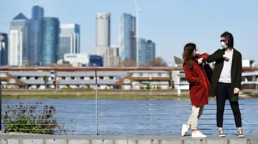 Two people don masks in London's Docklands