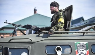 A Chechen special force trooper sits atop an APC decorated with a portrait of former Chechen president Akhmad Kadyrov, the father of the current Chechen leader Ramzan Kadyrov, during a traini