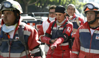 Mexican Red Cross members arrive at the premises of the building that houses the state-owned Mexican oil giant PEMEX, following a blast on the eve, in Mexico City on February 01, 2013. An exp