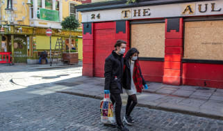 A couple wearing face masks carry a shopping bag as they pass a temporarily closed pub in Dublin.