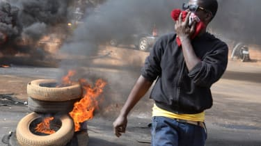 A man holds a hat over his mouth as black smoke billows from tyres set on fire in Niamey, on January 18, 2015 after police fired teargas to disperse a banned opposition demonstration in the c