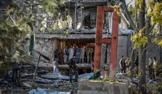 Afghan security personnel inspect the site near a car bomb explosion