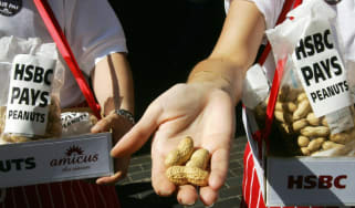 Striking HSBC employees offer peanuts to arriving HSBC shareholders outside the entrance to the Bank's AGM in London, 27 May