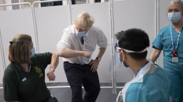 Boris Johnson bumps elbows with a first responder as she gets her vaccination