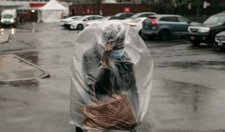 Woman covered in plastic bag wears mask to protect from Covid-19