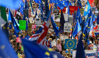 Demonstrators hold placards and EU flags as they take part in a march by the People's Vote organisation.