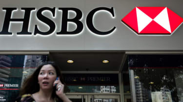 A woman talks on the phone near a branch of HSBC bank