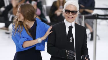 German fashion designer Karl Lagerfeld acknowledges the public along with British model Cara Delevingne at the end of the Chanel 2016 Spring/Summer ready-to-wear collection fashion show, on O