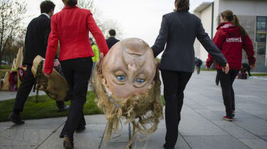 Ecological activists carry a giant head of Chancellor Angela Merkel ahead of a protest