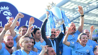 Man City manager Pep Guardiola lifts the Premier League trophy and celebrates with his staff
